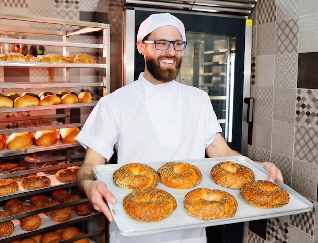 Привлекательный пекарь в белой форме держит поднос со свежеиспеченными рогаликами с кунжутом и маком