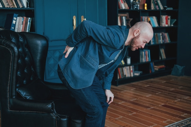 The attractive bald bearded man is holding onto his back, trying to get up from leather chair
