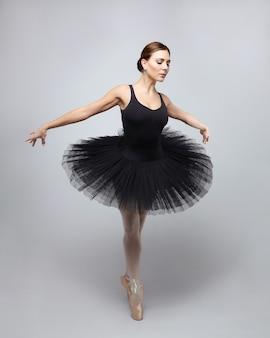 Привлекательная балерина изящно позирует в студии на белом фоне