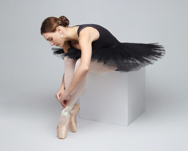 Привлекательная балерина изящно позирует, сидя на кубике. фотосессия в студии на белом фоне