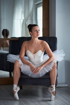 Attractive ballerina sitting on armchair with her legs opened and looking away thoughtfully. copyspace