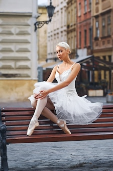 Attractive ballerina sitting on the bench in the city