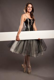 Attractive ballerina on tiptoe holding a white banner
