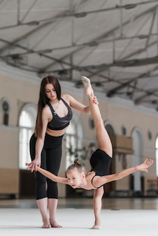 Attractive ballet dancer assisting her student on dance floor