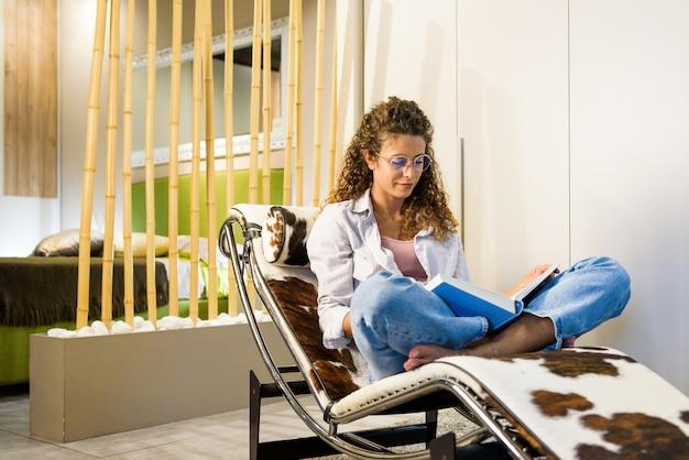 Привлекательная босиком женщина расслабляется, читая книгу на стильном современном кресле с откидной спинкой дома с тихой улыбкой удовольствия