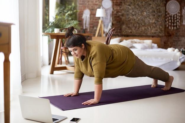 魅力的な裸足の若い太りすぎの女性は、ラップトップを介してオンラインビデオを見ながら、屋内でトレーニングしながらヨガマットで板をやっています。スポーツ、幸福、テクノロジー、アクティブで健康的なライフスタイルのコンセプト