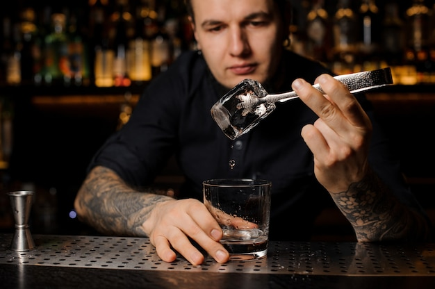 Attractive bartender adding to a drink in the glass a big ice cube with tweezers on the bar counter