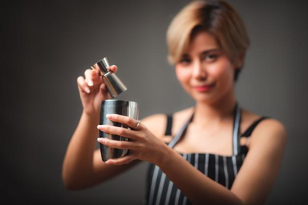 Привлекательная девушка-бармен держит в руках стальные коктейльные шейкеры за барной стойкой