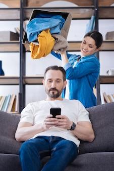 아내가 그에게 옷을 떨어 뜨리는 동안 매력적인 수염을 기른 자신감있는 남편이 코치에 앉아 전화로 연주
