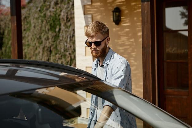 Ragazzo attraente hipster con la barba in tonalità nere in piedi in macchina con il braccio teso