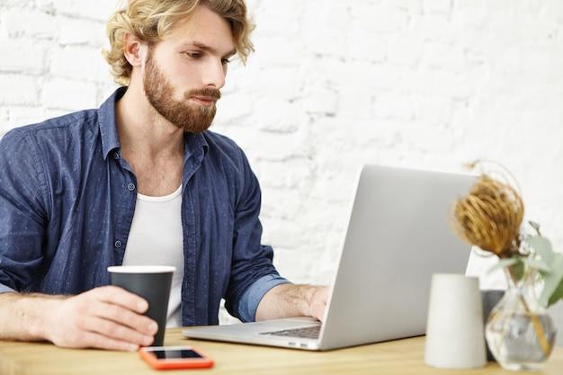 Imprenditore maschio barbuto attraente che beve tè o caffè mentre lavorando al computer portatile generico durante il pranzo al caffè moderno. giovane lavoratore indipendente serio che per mezzo del pc portatile per lavoro distante