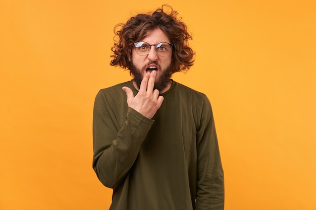 Attractive bearded male in glasses puts fingers in mouth showing nausea