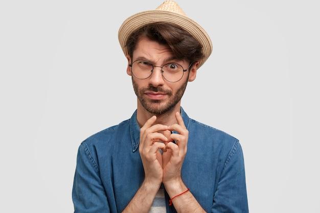 Attraente maschio barbuto tiene le mani unite e guarda con sguardo intrigante