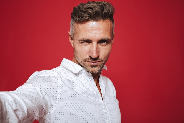 Привлекательный бородатый мужчина 30-х годов в белой рубашке, делающий селфи на красном фоне