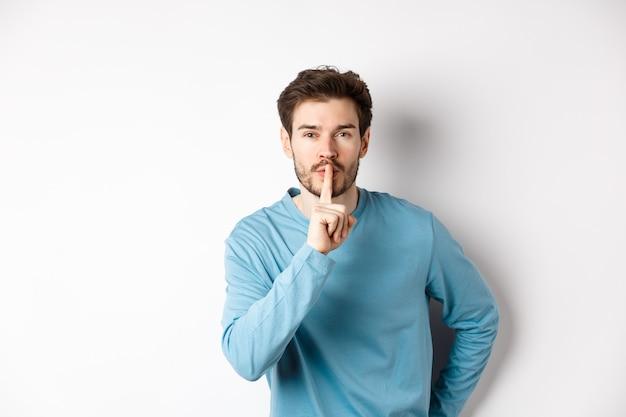 Привлекательный бородатый мужчина просит молчать, показывая жест запрета тишины и глядя на камеру спокойно, стоя на белом фоне.
