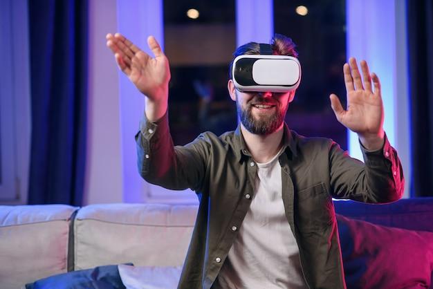 魅力的なひげを生やした男性が夕方に自宅で仮想現実の眼鏡を楽しんでいます。 vrゴーグルヘッドセットとスマートフォンの使用。