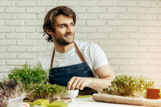 Привлекательный бородатый фермер заботится о ростках микрозелени