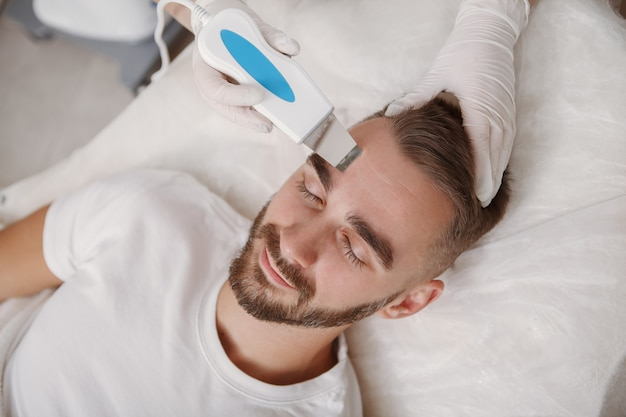 Attractive bearded man getting skin ultrasound cleanse by cosmetician