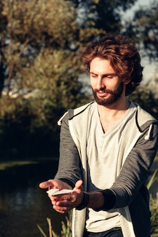 Attractive bearded man holding paper airplane