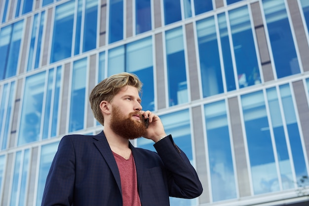 Attraente uomo barbuto parla dal telefono cellulare vicino edificio commerciale con grandi finestre blu