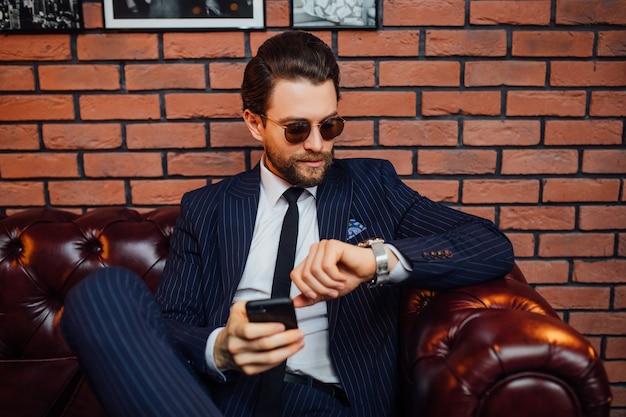Привлекательный бородатый мужчина в костюме, сидя на кожаном диване, держа смартфон. комфорт и расслабление.