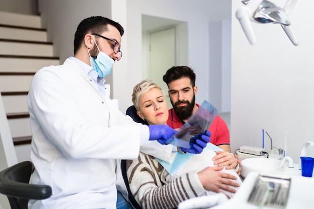 歯科医院で治療を受けている妊娠中の妻と魅力的なひげを生やした男。