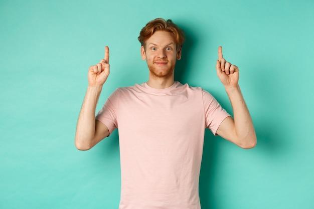 빨간 머리를 가진 매력적인 수염 난된 남자, 티셔츠를 입고 명랑하고 손가락을 가리키는, 광고 표시, 청록색 배경 위에 서.