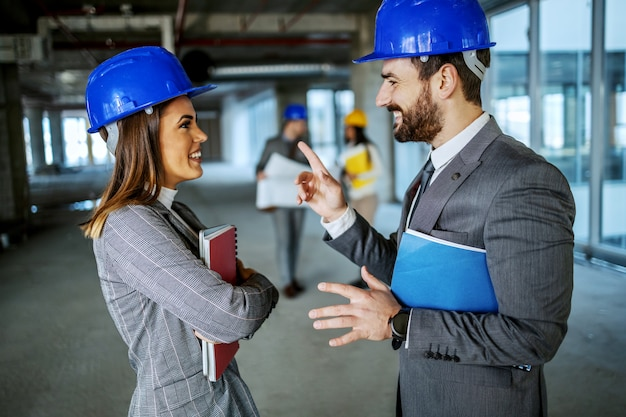 Attractive bearded real estate agent holding paperwork under armpit and talking with his charming female colleague about value of property. building in construction process interior.