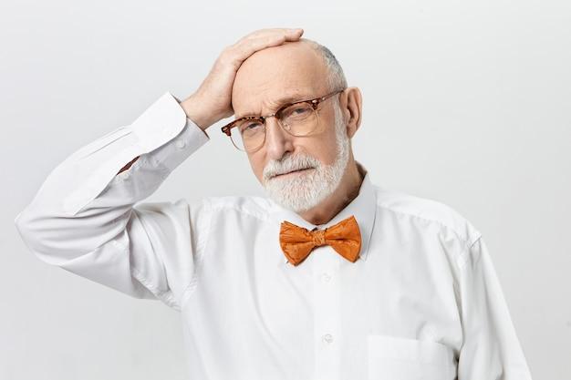 Attraente maschio barbuto in pensione che indossa una camicia bianca e farfallino arancione che tiene la mano sulla sua testa calva, sentendosi triste perché è invecchiato troppo velocemente. concetto di età, pensionamento e maturità
