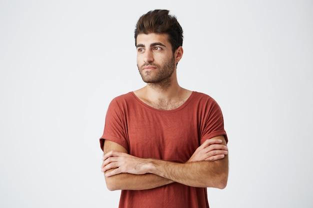 Привлекательный бородатый загорелый человек, с удовольствием смотреть скрещенными руками на белой стене. студент в повседневной футболке ждет свою подругу
