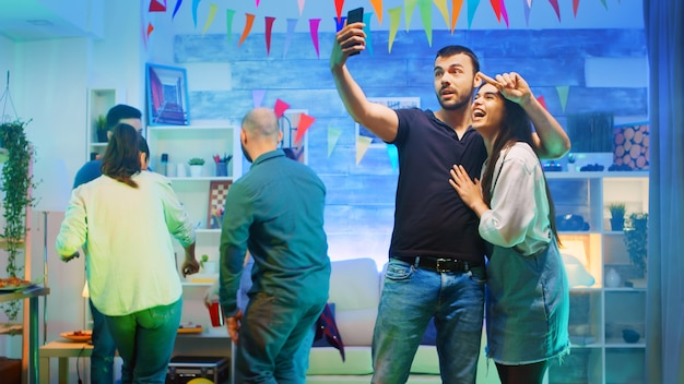 Attractive bearded young man taking a selfie with beautiful friend at the party. loud music at wild college party in a room with neon lights, disco ball and a lot of alcohol