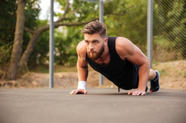 Привлекательный бородатый молодой спортсмен делает отжимания на открытом воздухе
