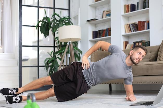 検疫中に自宅で板運動をしている魅力的なクマの男。フィットネスは健康の鍵です