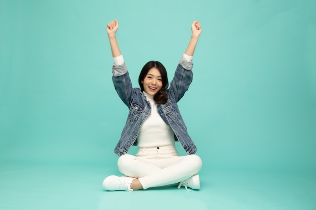매력적인 아름다운 아시아 여성이 바닥에 앉아 녹색 배경에 고립된 행복에서 팔을 들고 흥분한 사업가 우승자 성공 개념