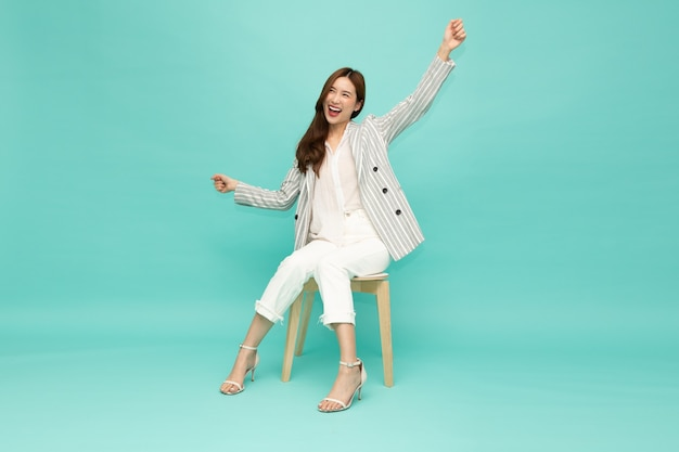 Attractive beautiful asian woman sitting on white modern chair and hands up raised arms from happiness excited
