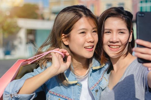 도시에서 쇼핑하는 동안 스마트 폰을 사용하는 매력적인 아름다운 아시아 여자