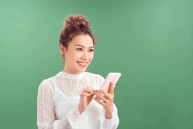 Привлекательная красивая азиатская женщина с помощью мобильного телефона, улыбаясь, изолированные на зеленом фоне.