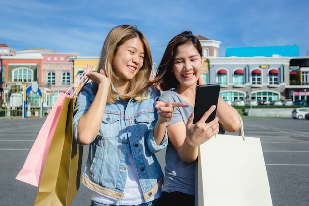 Attractive beautiful asian woman using a smartphone while shopping in the city