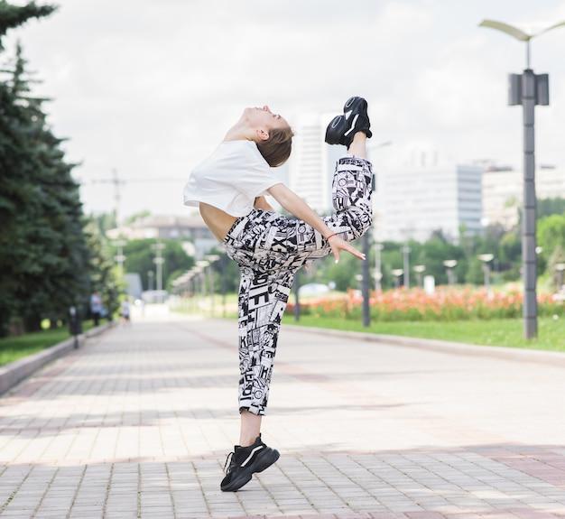 魅力的な美しい白人の女の子が通りで踊っています。スポーツ、ダンス、都市文化。ファッションライフスタイル。