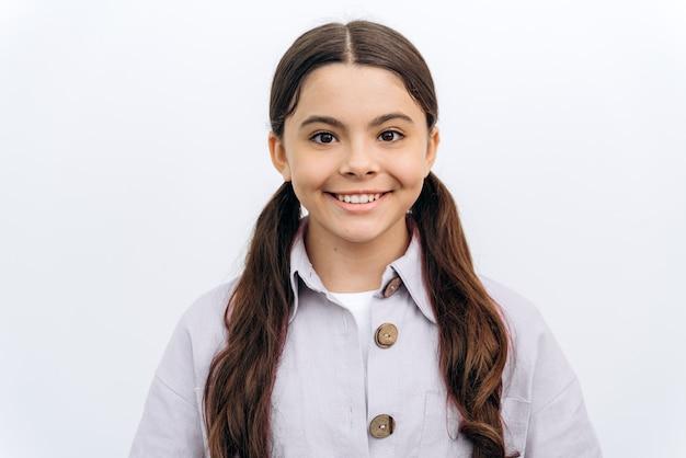 흰색 배경에 웃고 있는 매력적이고 아름다운 귀여운 소녀. 빈 벽을 배경으로 포즈를 취하는 매력적인 흑인 소녀
