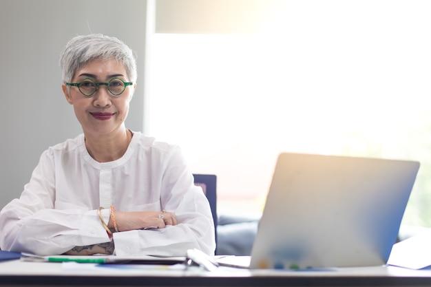 現代のホームオフィスでラップトップコンピューターに取り組んでいる魅力的な美しい成熟したビジネス女性。