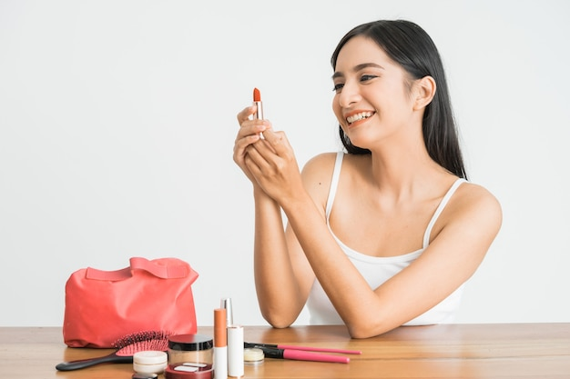 Attractive beautiful mixed race asian woman applying lipstick on her lips over white wall