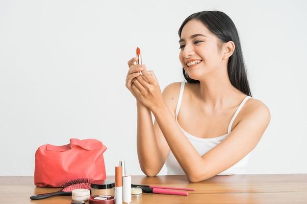 흰 벽에 그녀의 입술에 립스틱을 적용하는 매력적인 아름다운 혼혈 아시아 여자