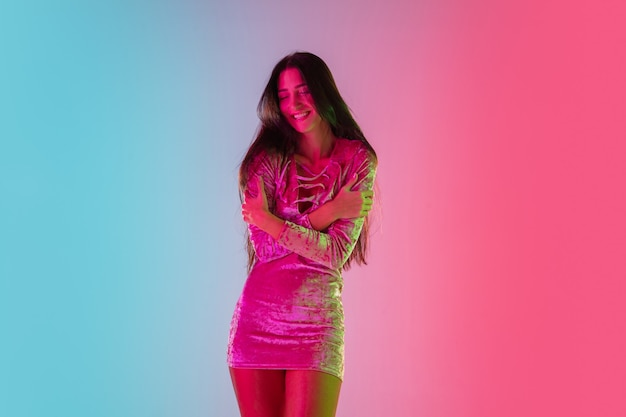Attractive. beautiful seductive girl in fashionable dress, outfit on gradient pink-blue background in neon light. half-length portrait. copyspace for ad. summer, fashion, beauty, emotions concept.