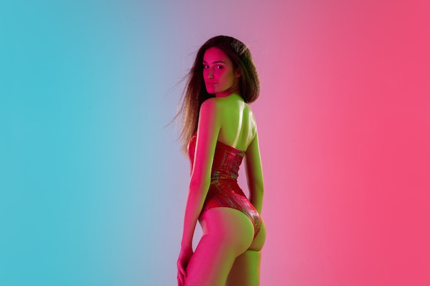Attractive. beautiful seductive girl in fashionable red swimsuit on gradient pink-blue background in neon light. half-length portrait. copyspace for ad. summer, fashion, beauty, emotions concept.