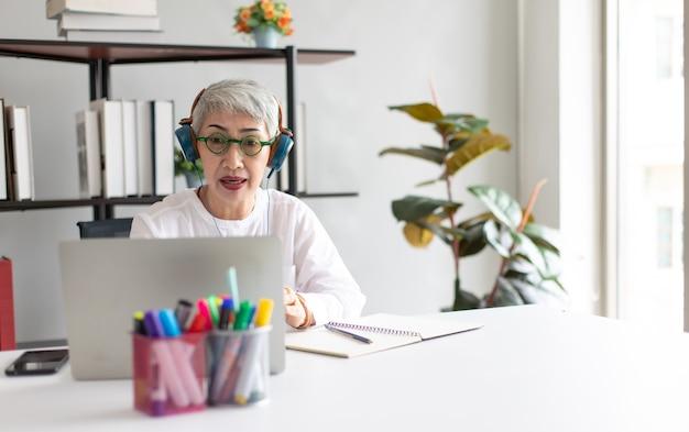 自宅でオンラインビデオ会議にラップトップコンピューターを使用して魅力的な美しいシニアスタイリッシュなビジネス女性