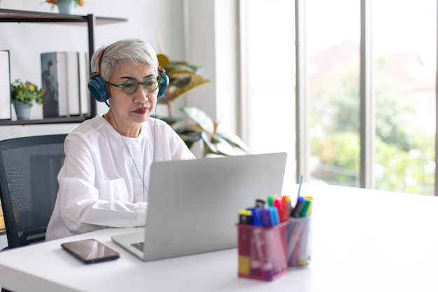 Attractive beautiful senior stylish business woman using laptop computer for online video conference at home