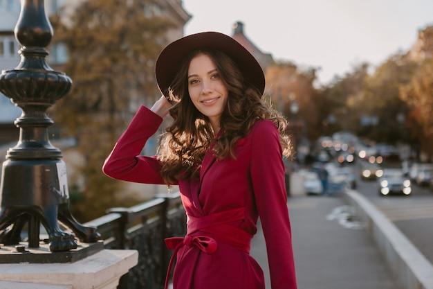 Attraente bella donna alla moda in vestito viola che cammina nella via della città, tendenza di moda primavera estate autunno stagione indossando il cappello, tenendo la borsa