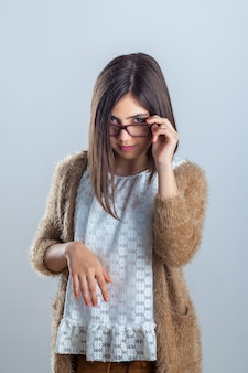 Attractive and beautiful teenager girl in glasses posing in front of the camera in the studio.