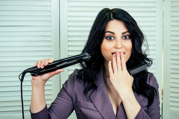 매력적인 아름다운 여성 미용사 스타일리스트는 미용실에서 머리를 손질하고 머리카락을 위해 컬링 아이언을 들고 있습니다.